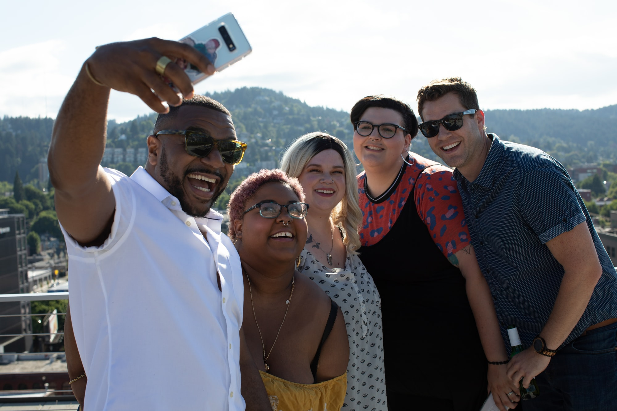 Plus size women with friends on rooftop with city view taking selfie with cell phone