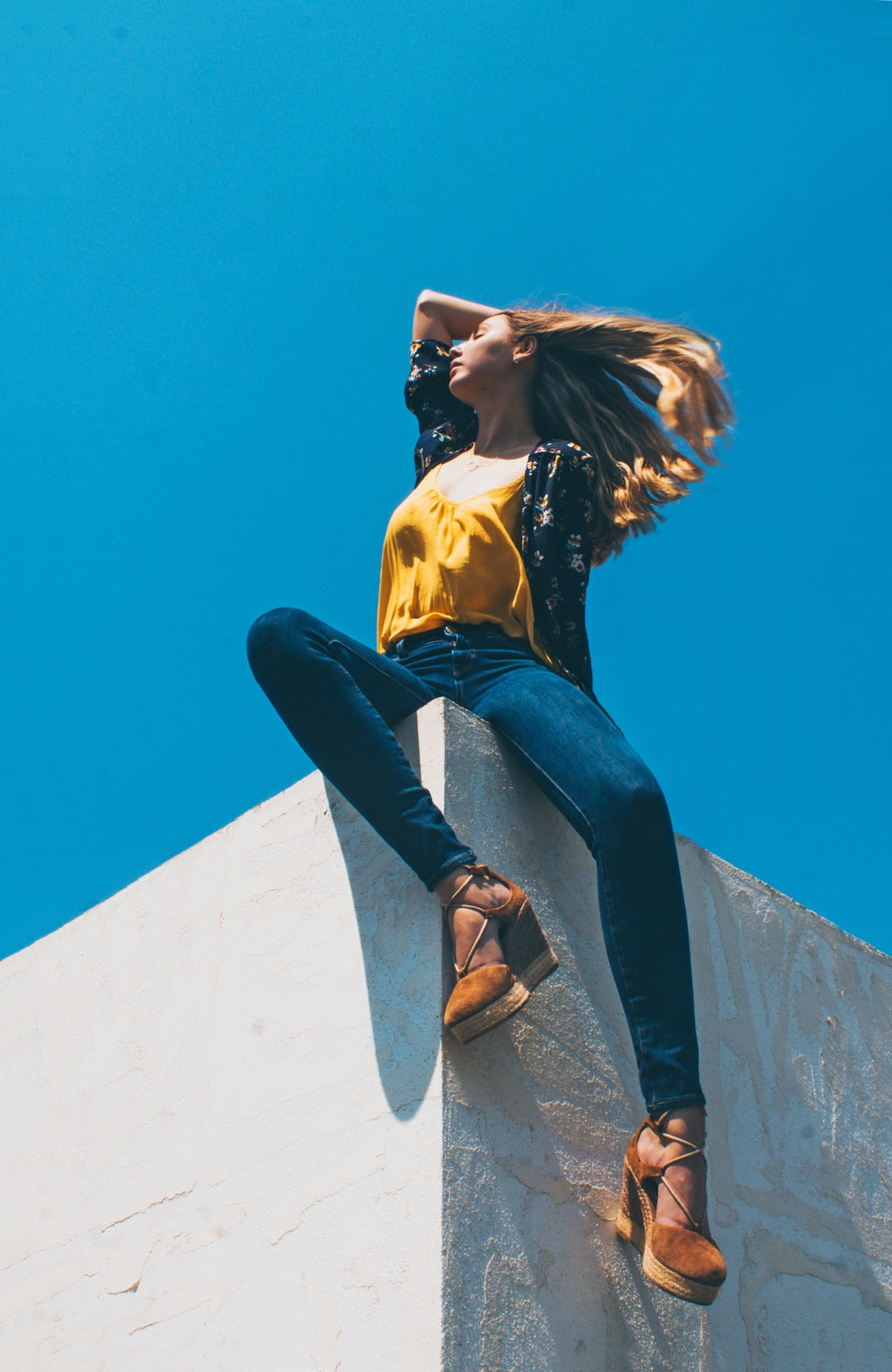 woman in yellow shirt and blue denim jeans sitting on edge at daytime
