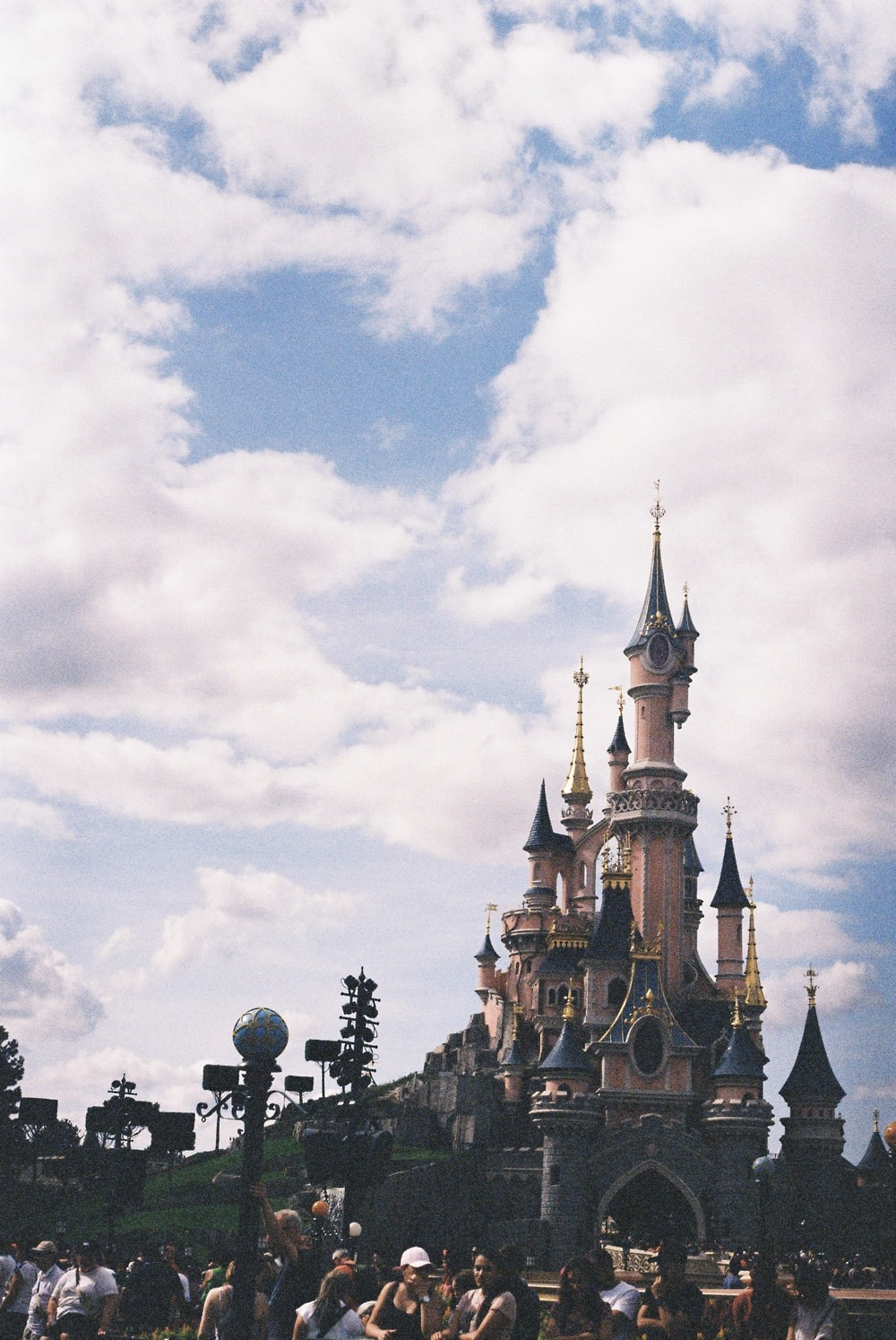 pink and blue Disneyland castle under white and blue cloudy sky