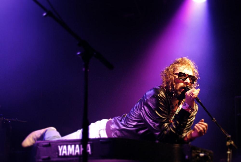 man singing while planking on Yamaha piano