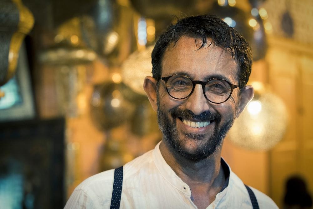 man wearing white shirt and eyeglasses smiling