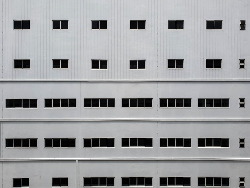 white concrete building with rows of glass windows