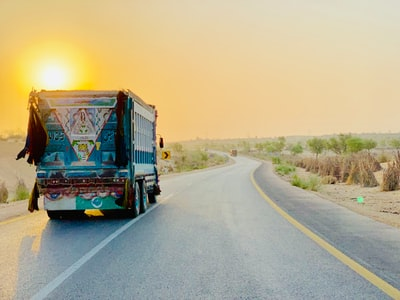 white and blue truck on gray pavement road pakistan teams background