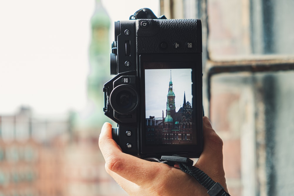 person holding camera with tower photo