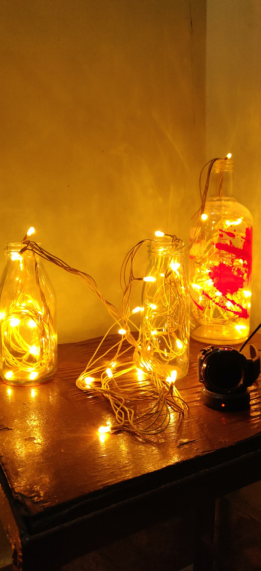 three clear glass bottles with yellow string lights
