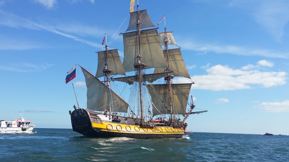 brown and yellow ship on body of water during daytime