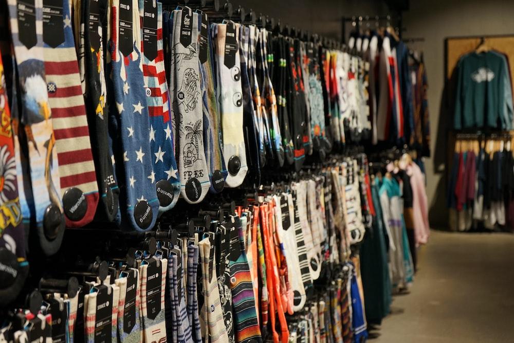 assorted clothes hung on display racks