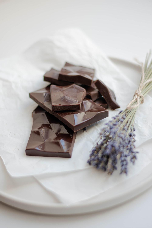 chocolate bars beside flower on white tray