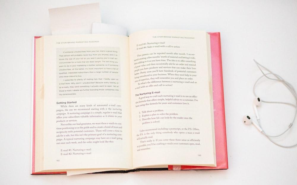 open book beside earphones on white surface