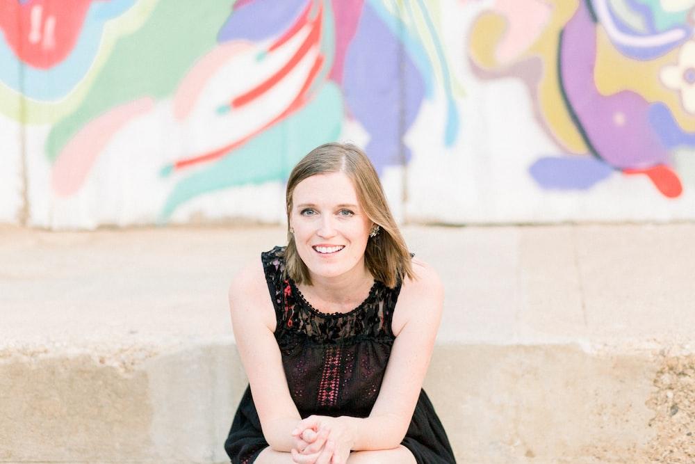 smiling woman wearing black sleeveless dress sitting in front of graffiti