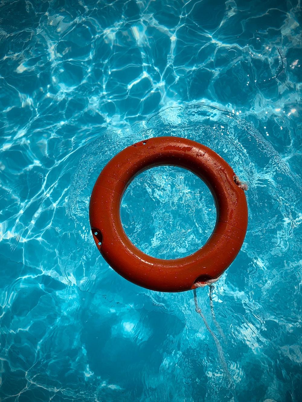 round red swim ring on body of water