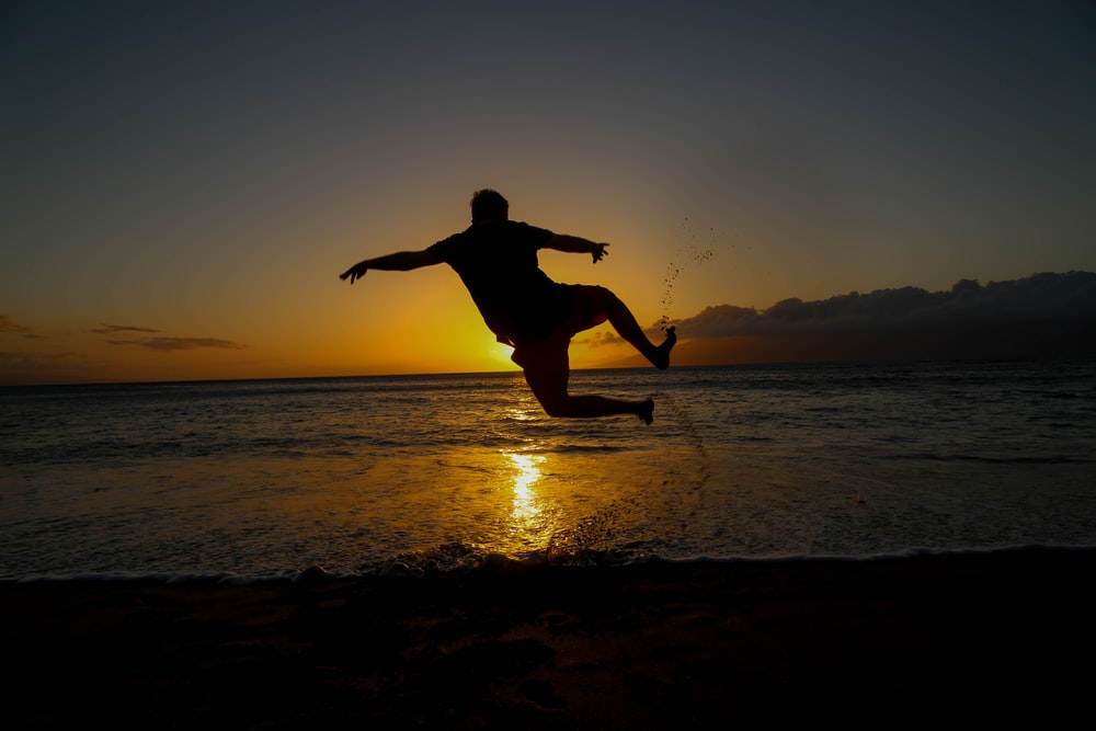 silhouette of jumping man on seashore during golden hour