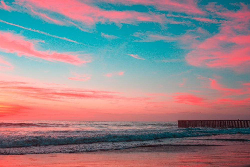 body of water under pink and blue sky during golden hour