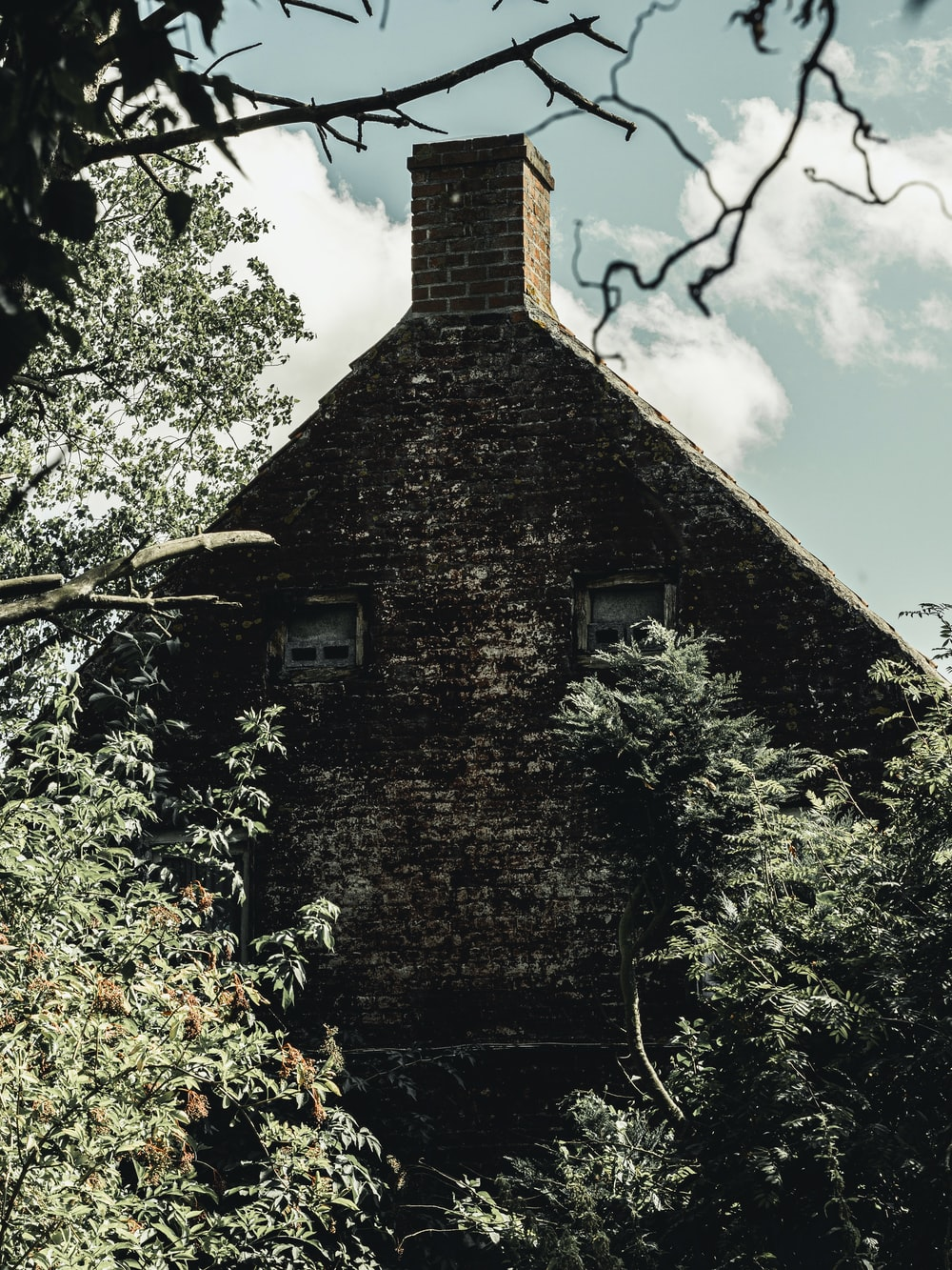 gray bricked house with chimney beside trees during daytime