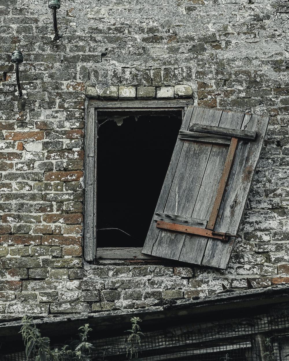 gray stone building showing open grey wooden window