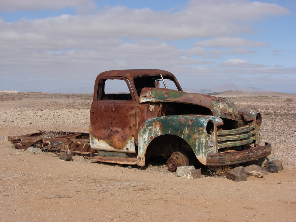 green rusted classic truck lying on desert without wheels