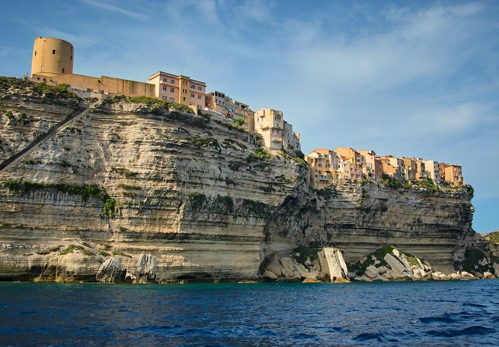 beige concrete buildings near rock cliff