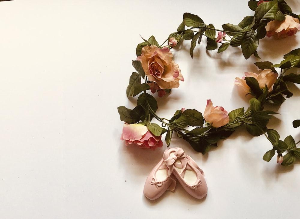 pair of pink ballerina flats ceramic figurine besides flower wreathes