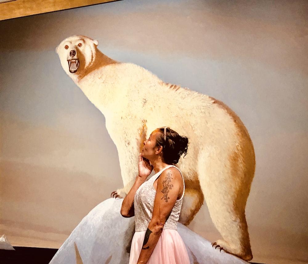 woman wearing white sleeveless dress besides photo of white polar bear