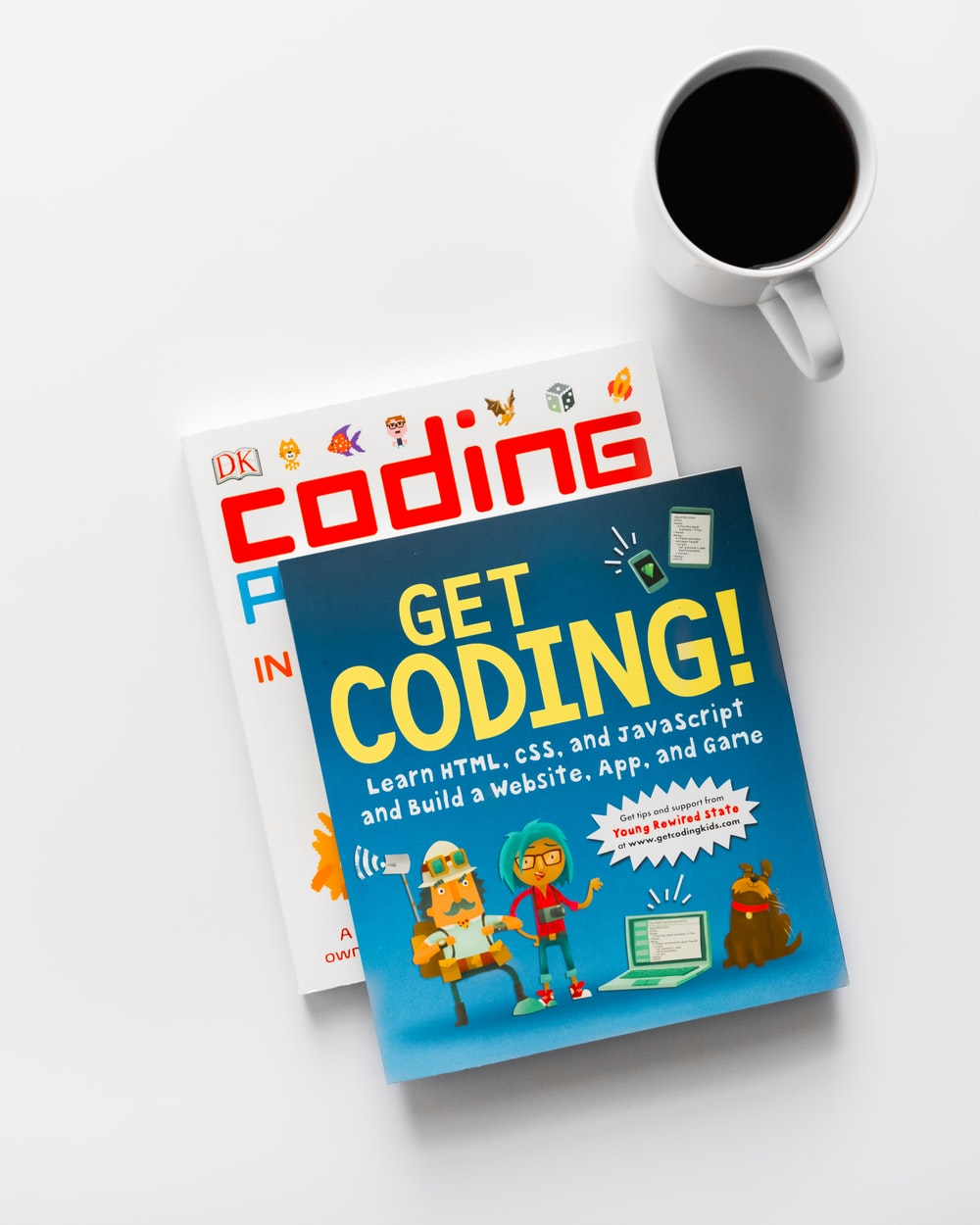 Get Coding and Coding books beside cup of coffee