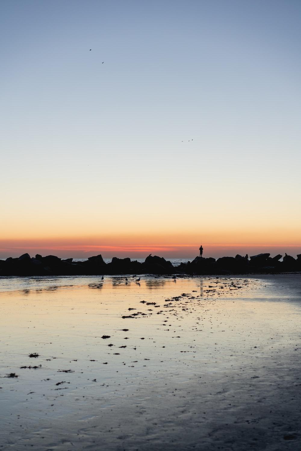 silhouette of sea under orange skies