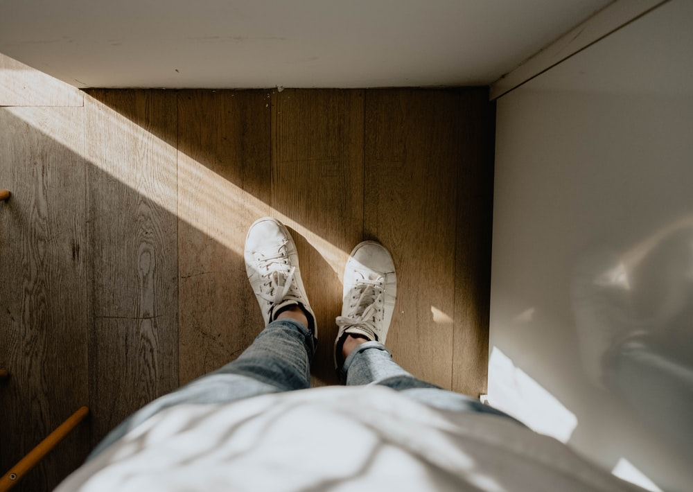 person wearing pair of white shoes standing on brown wood parquet floor