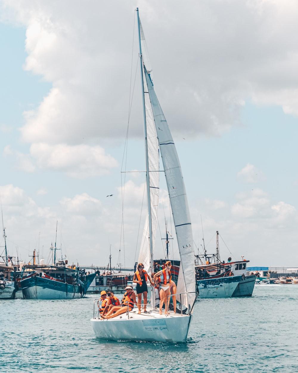 Persone su una barca a vela bianca vicino al porto