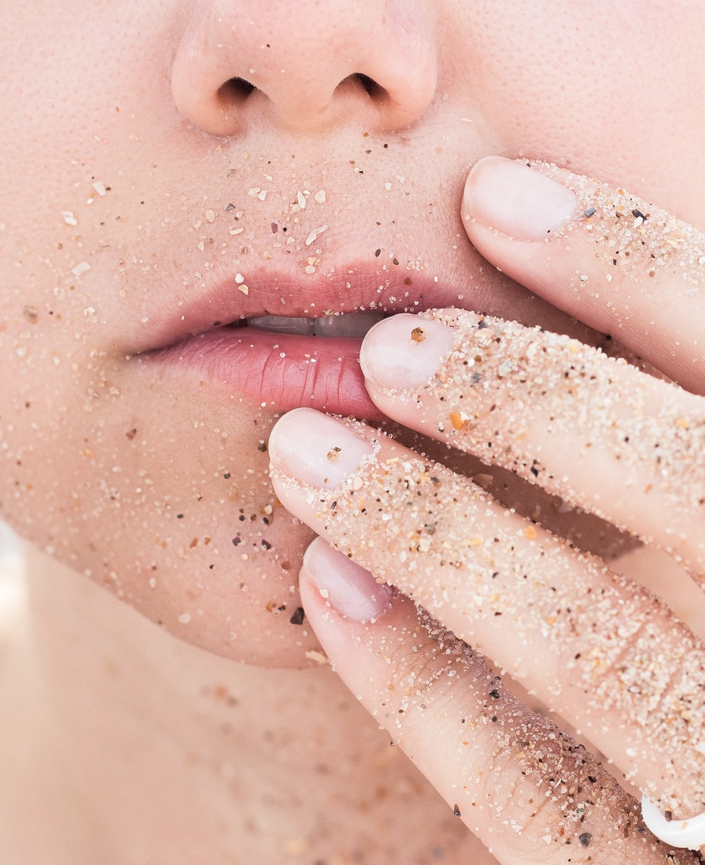 person holding lips covered in sands