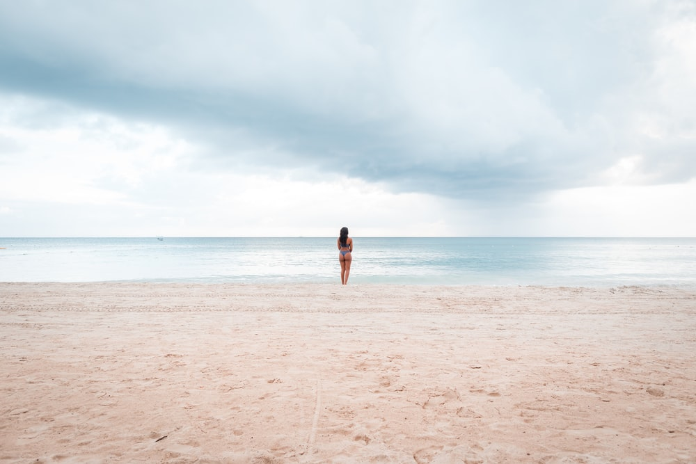 person standing on seashore during daytime