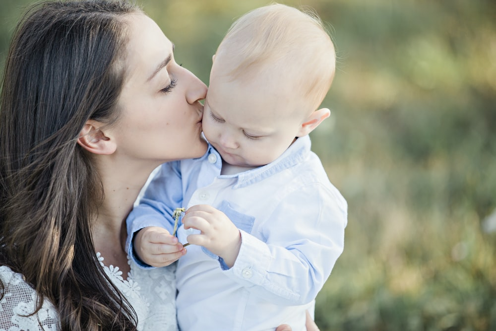 selective focus photography of woman kissing baby