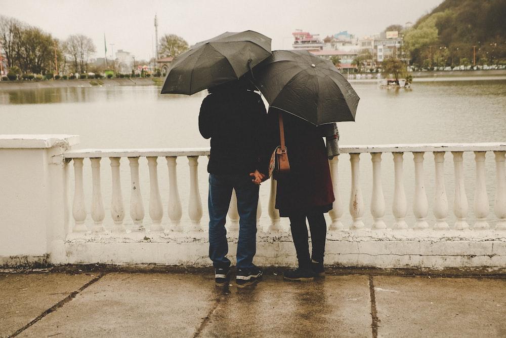 man and woman holding black umbrellas