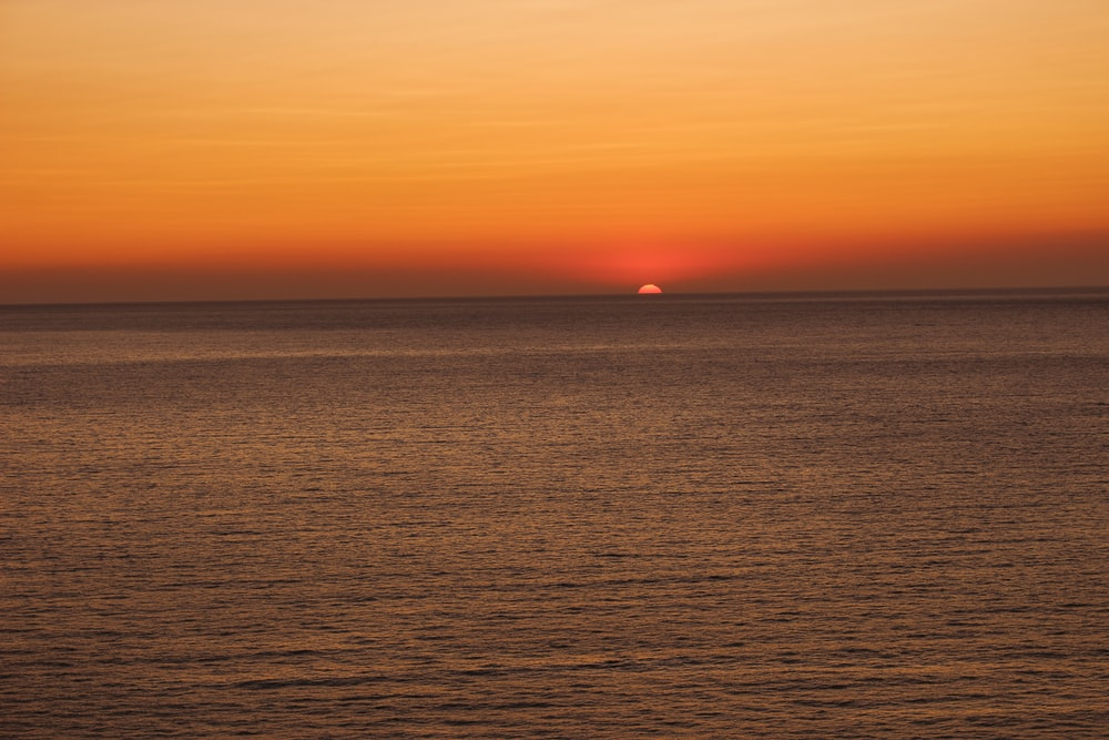 photograph of ocean during sunset