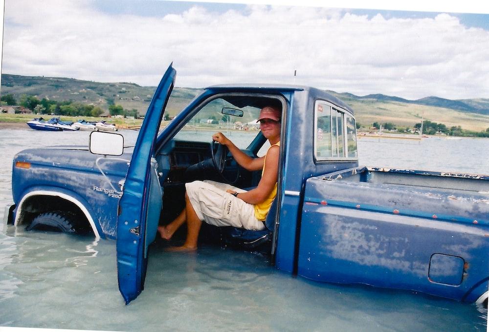 man inside blue pickup truck