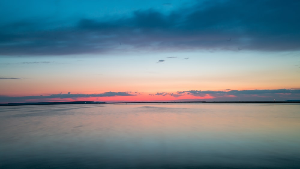 blue calm sea under orange and blue skies
