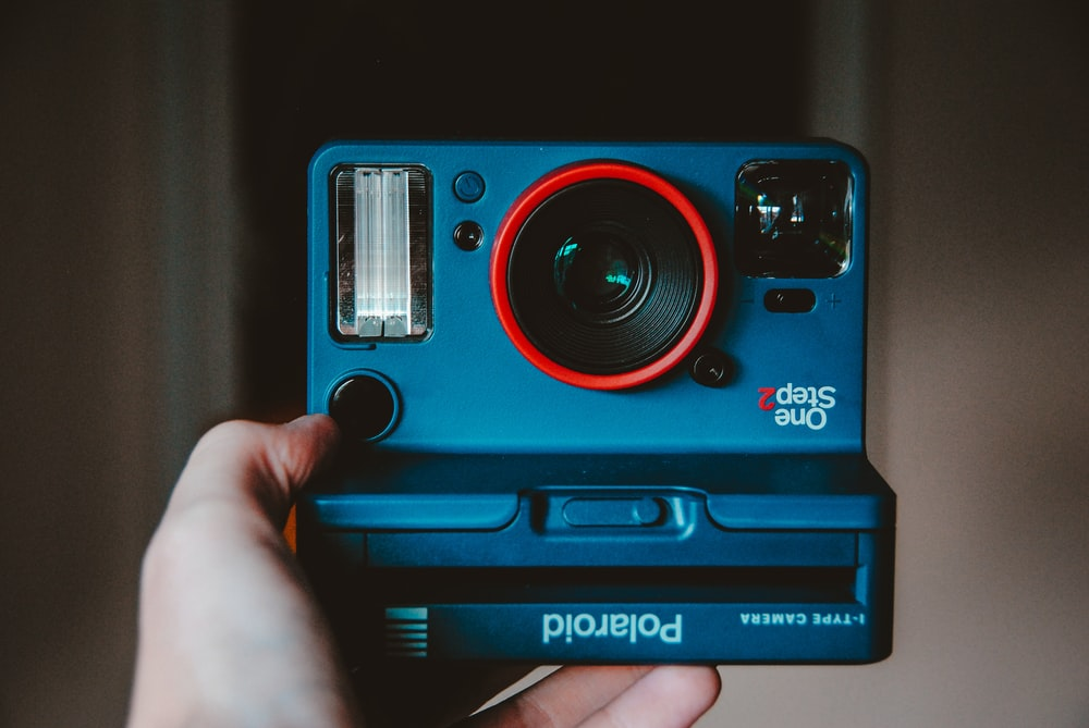 blue, black, and red Polaroid One Step camera