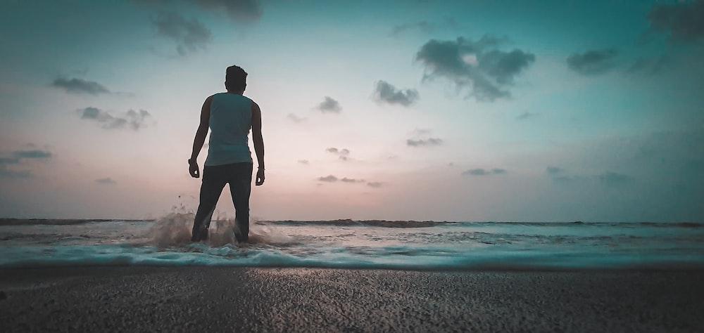 man wearing white sleeveless shirt standing on seashore