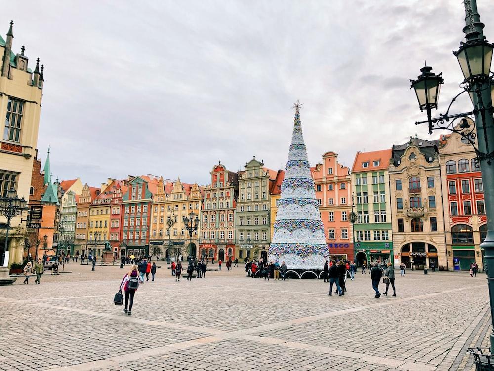 people walking beside giant Christmas tree