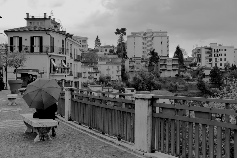 grayscale photography of person sitting on bench with umbrella