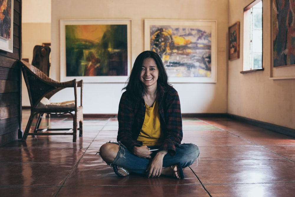 smiling woman sitting on floor near armchair indoors