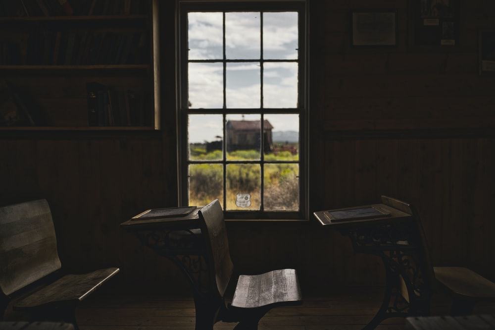 brown wooden desks and clear glass window