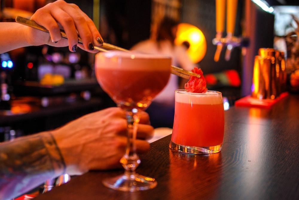 bartender putting red ingredient on cocktail drinks