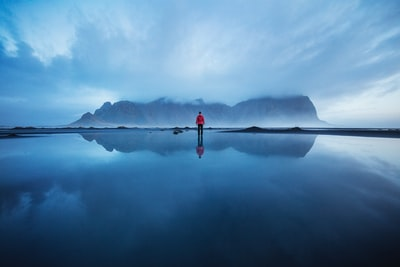Joshua Earle standing in still waters before the Vestrahorn in Iceland. Explore more Huper Photos at explorehuper.com/photos 🚀