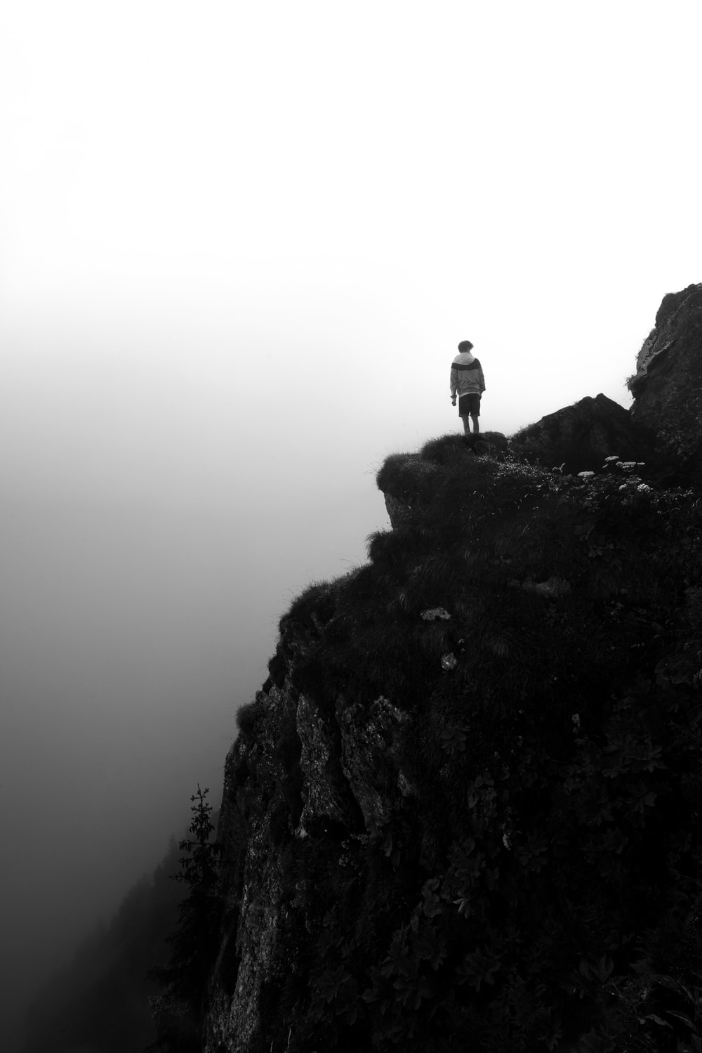 grayscale photography of person standing on cliff