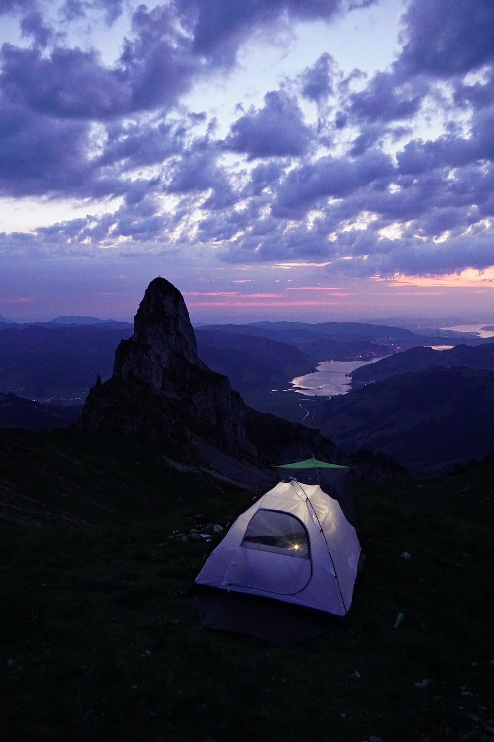 lighted tent on mountain top under clouded sky