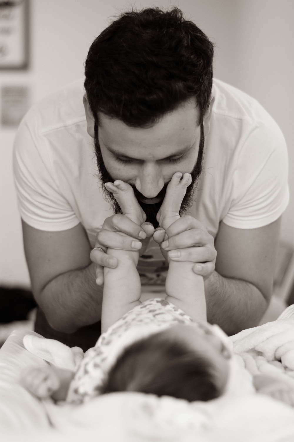 grayscale photography of man playing with baby
