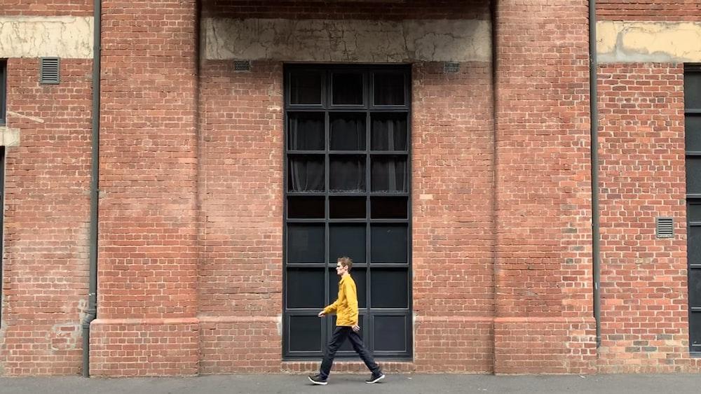 man walking beside wall