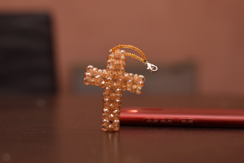 gold-colored cross with white pearls macro photography