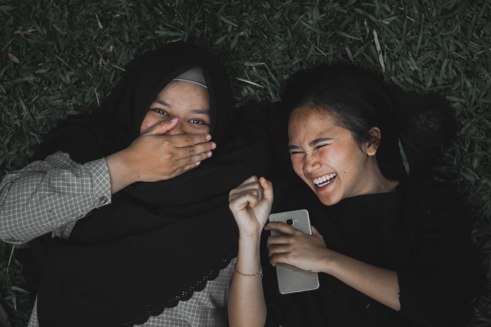 smiling women lying on ground