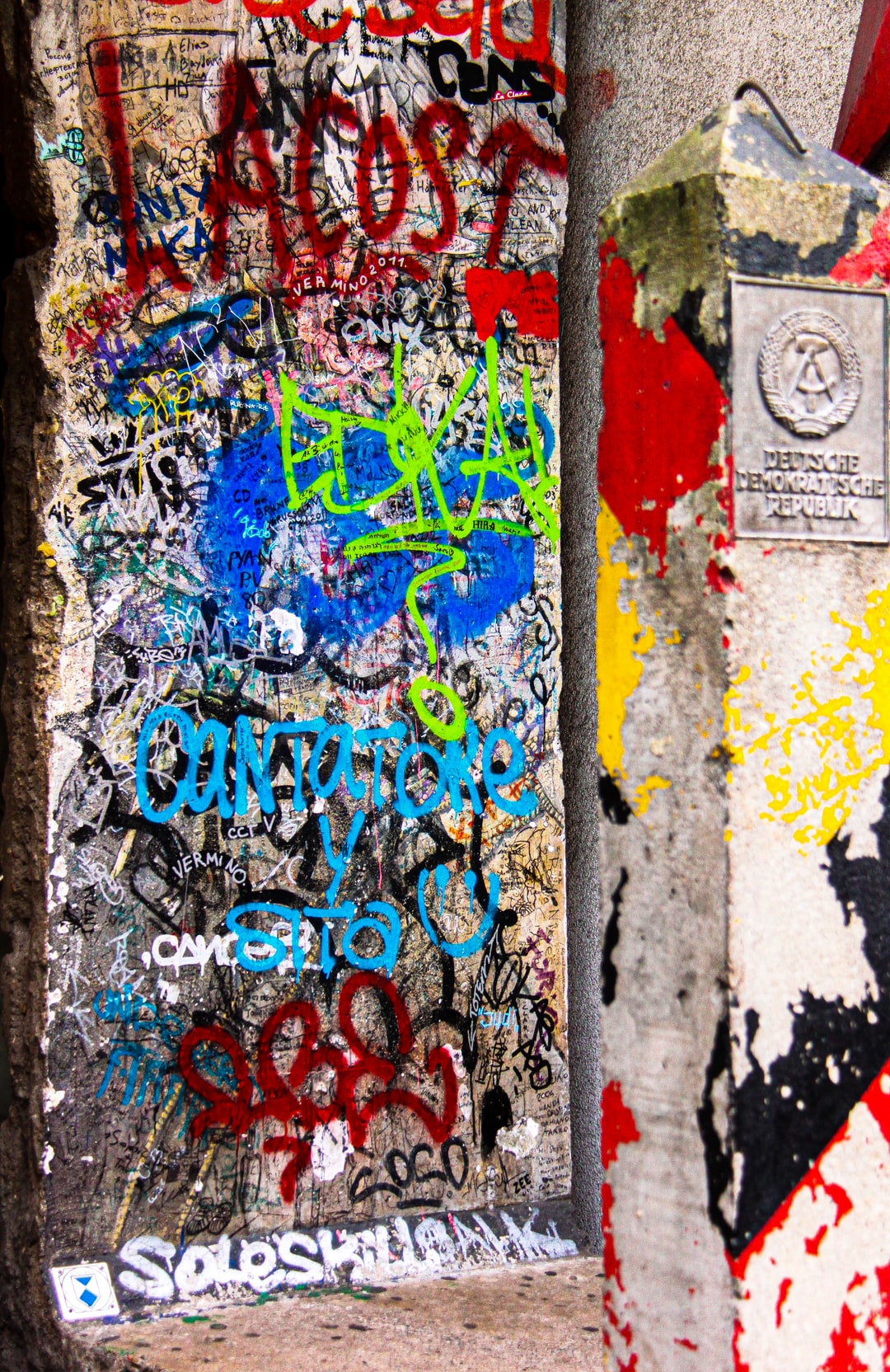 Sprayed graffiti piece of the Berlin wall close to Checkpoint Charly as symbol of World War II Berlin, Germany.