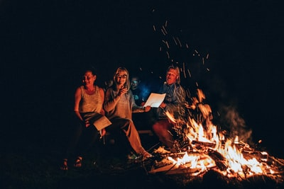 people sits in front of fire bonfire teams background